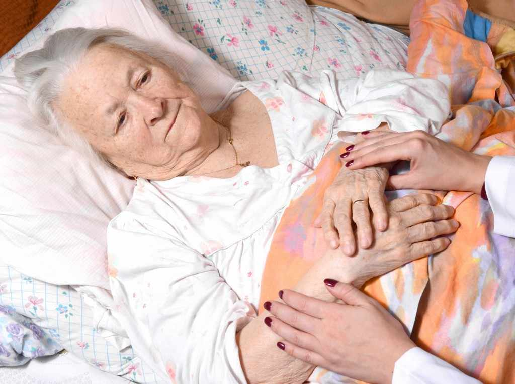 an elderly woman in bed, with a caretaker holding her hands