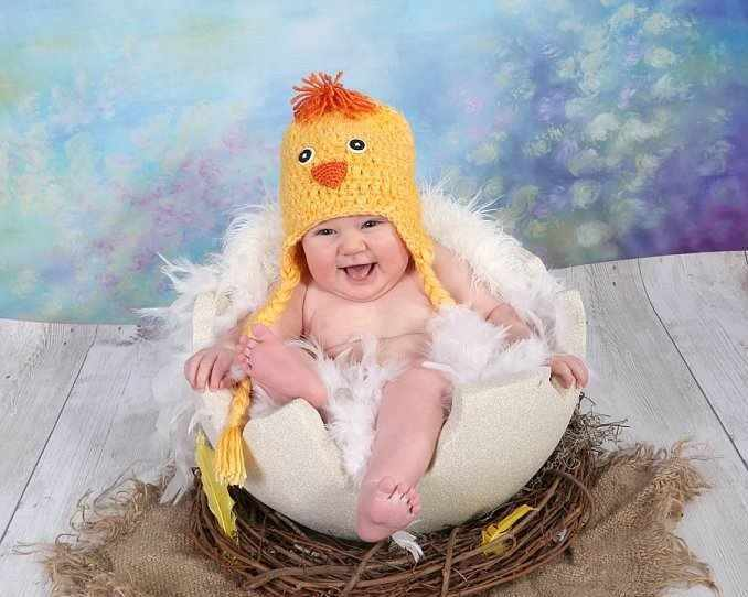 a little baby in a chicken costume sitting in an egg nest