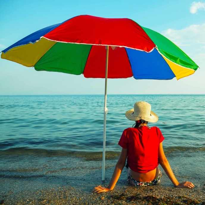person sitting on the beach in a hat under the shade of an umbrella