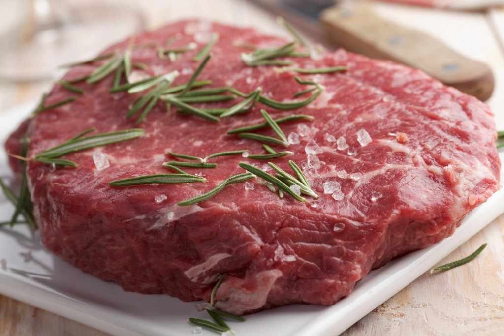 raw beef steak with salt and rosemary