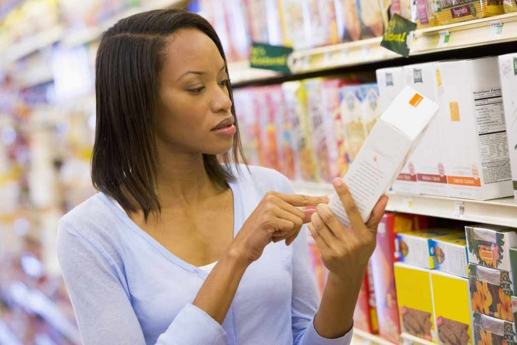 a woman shopper checking food labels in the supermarket
