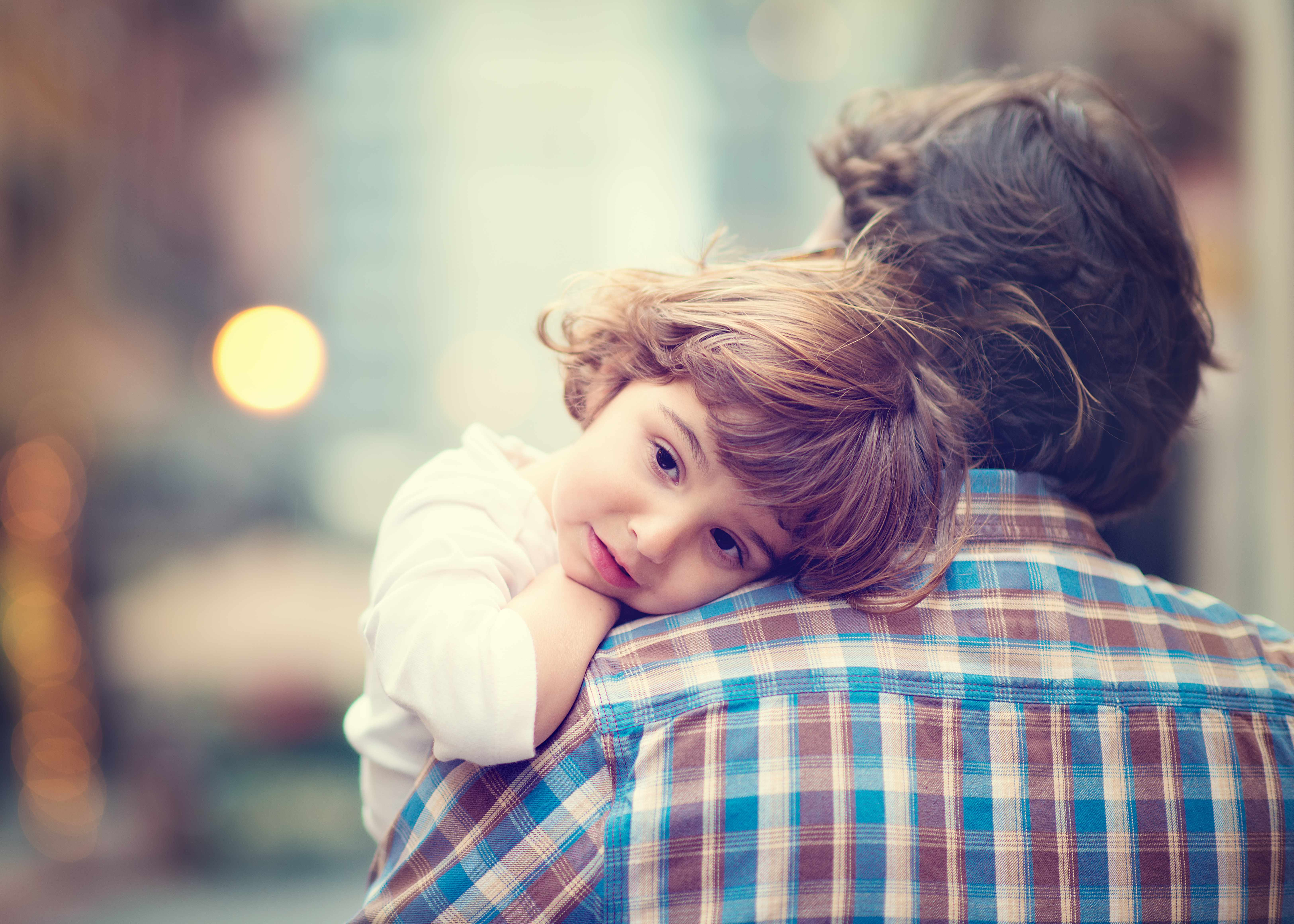 a little girl in a adult person's arms resting her head on his shoulde