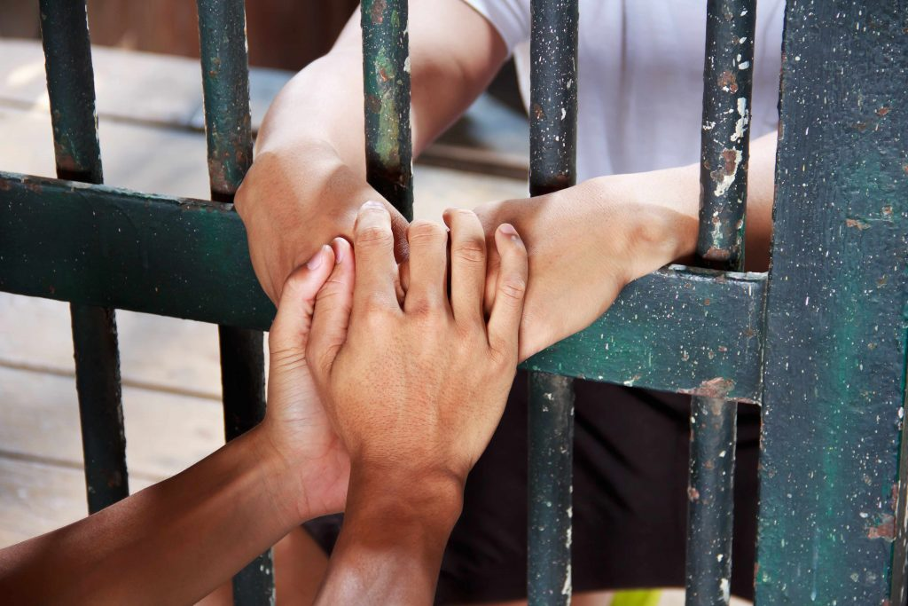 a person in jail behind bars with another person reaching in to hold their hands with kindness and forgiveness