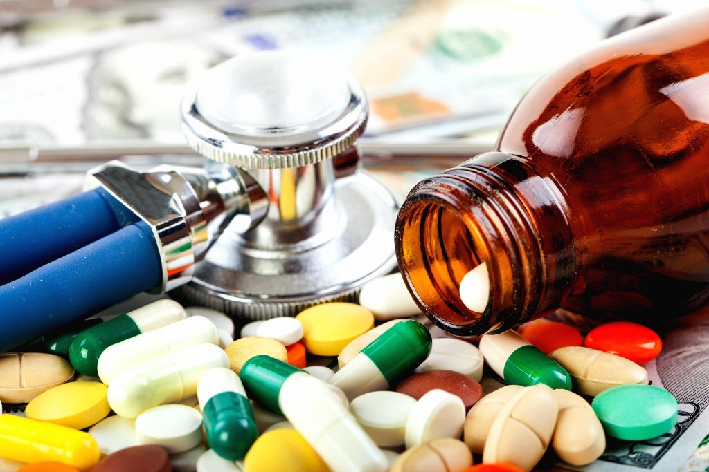 a pill bottle spilling prescription medicine, antibiotics, with a stethoscope nearby