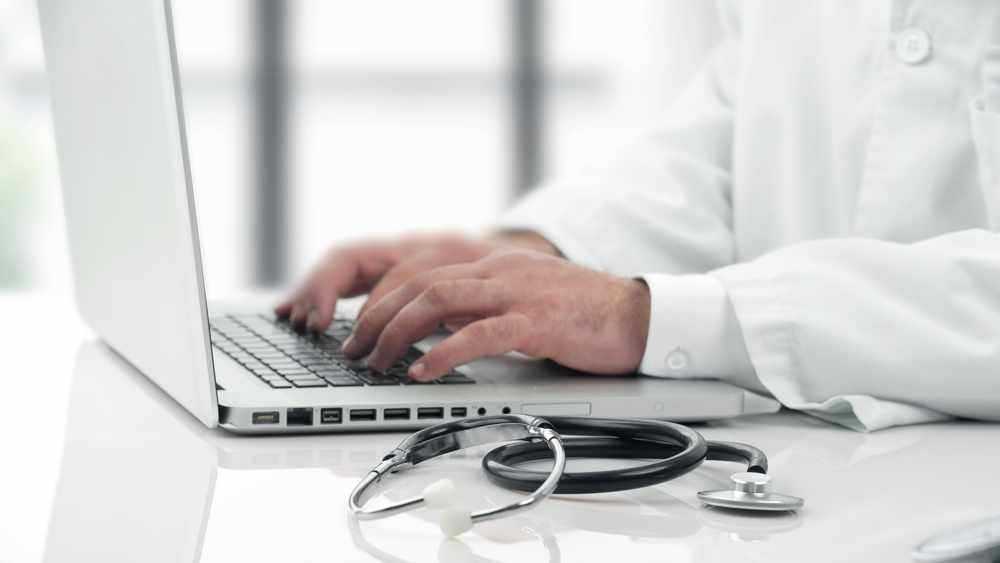Physician at laptop with stethoscope nearby