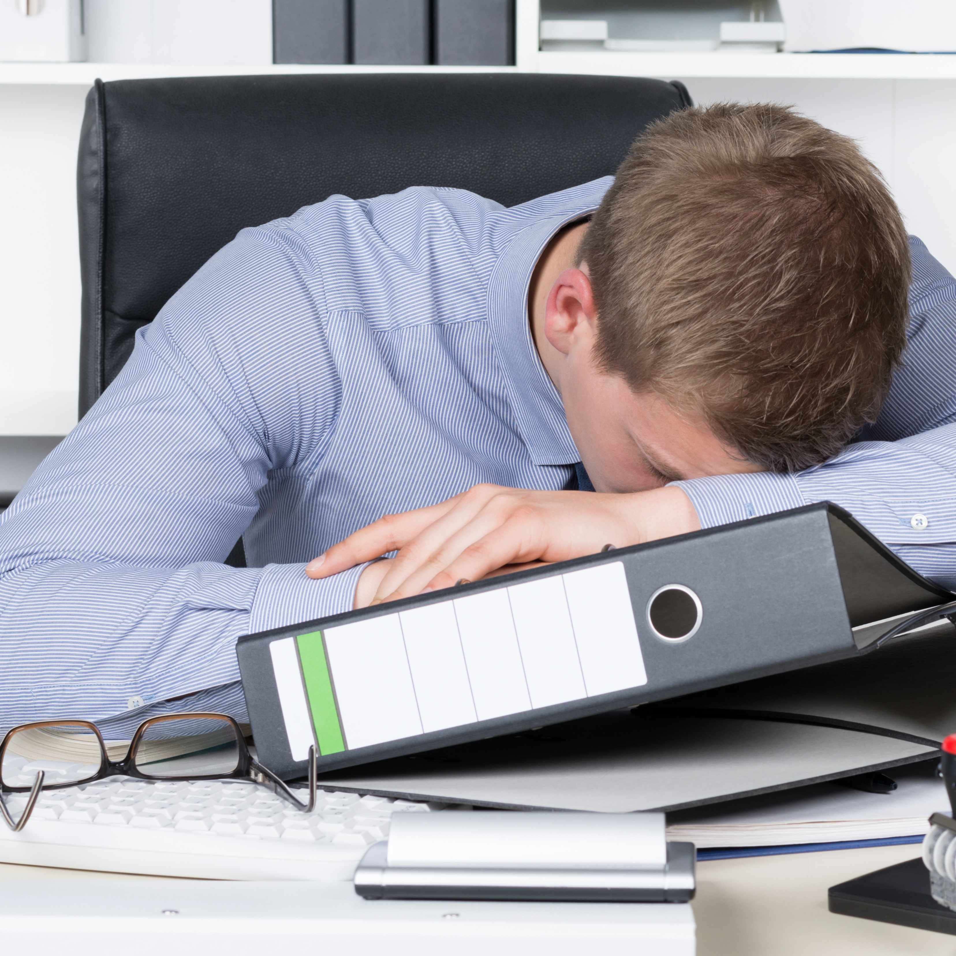 a businessman tired and resting on his desk with a pile of work