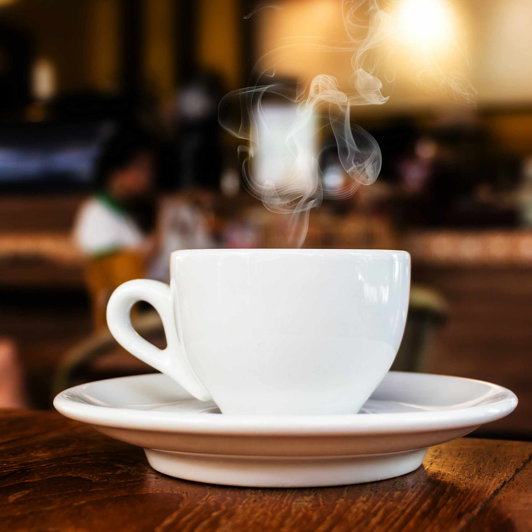 a cup of coffee or tea sitting on a wood table