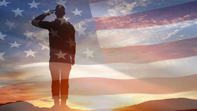 a soldier saluting at sunset with the United States flag superimposed over the photo