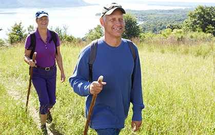 a woman and a man hiking on a grassy hillside, enjoying exercise