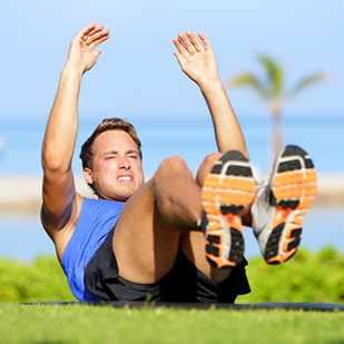 a man doing sit-ups exercising a workout outdoors
