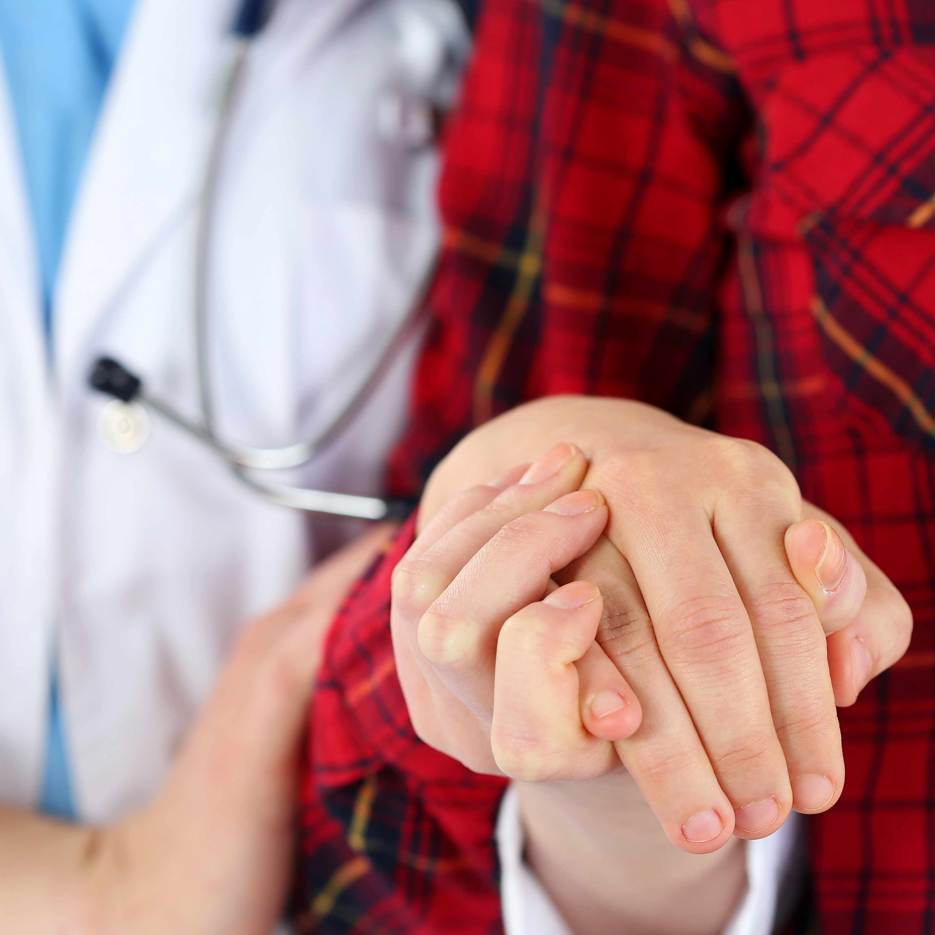 a medical staff member, doctor or nurse, holding patient's hand and helping the person walk