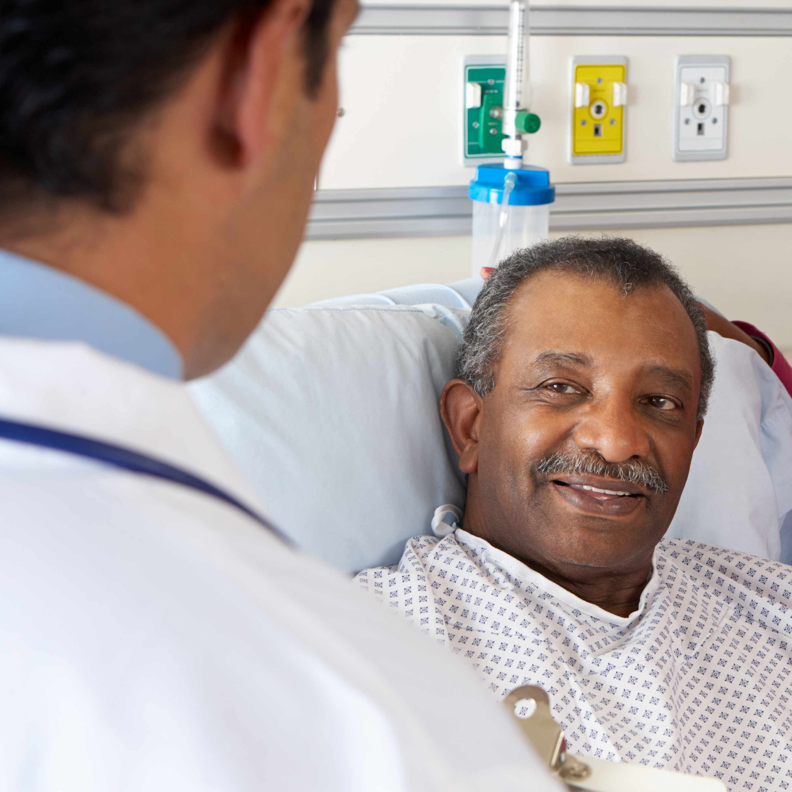 middled-aged African-American man in hospital bed, with his wife talking with doctor