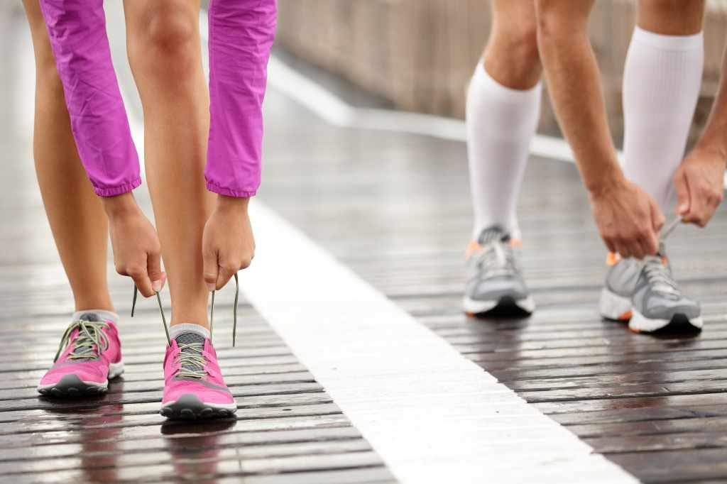runners tying laces on running shoes