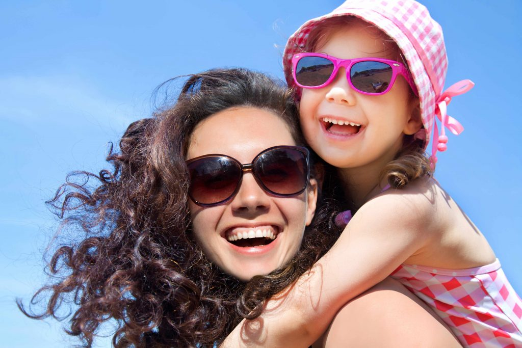 a young woman carrying a child on her back, both in the sun wearing sunglasses