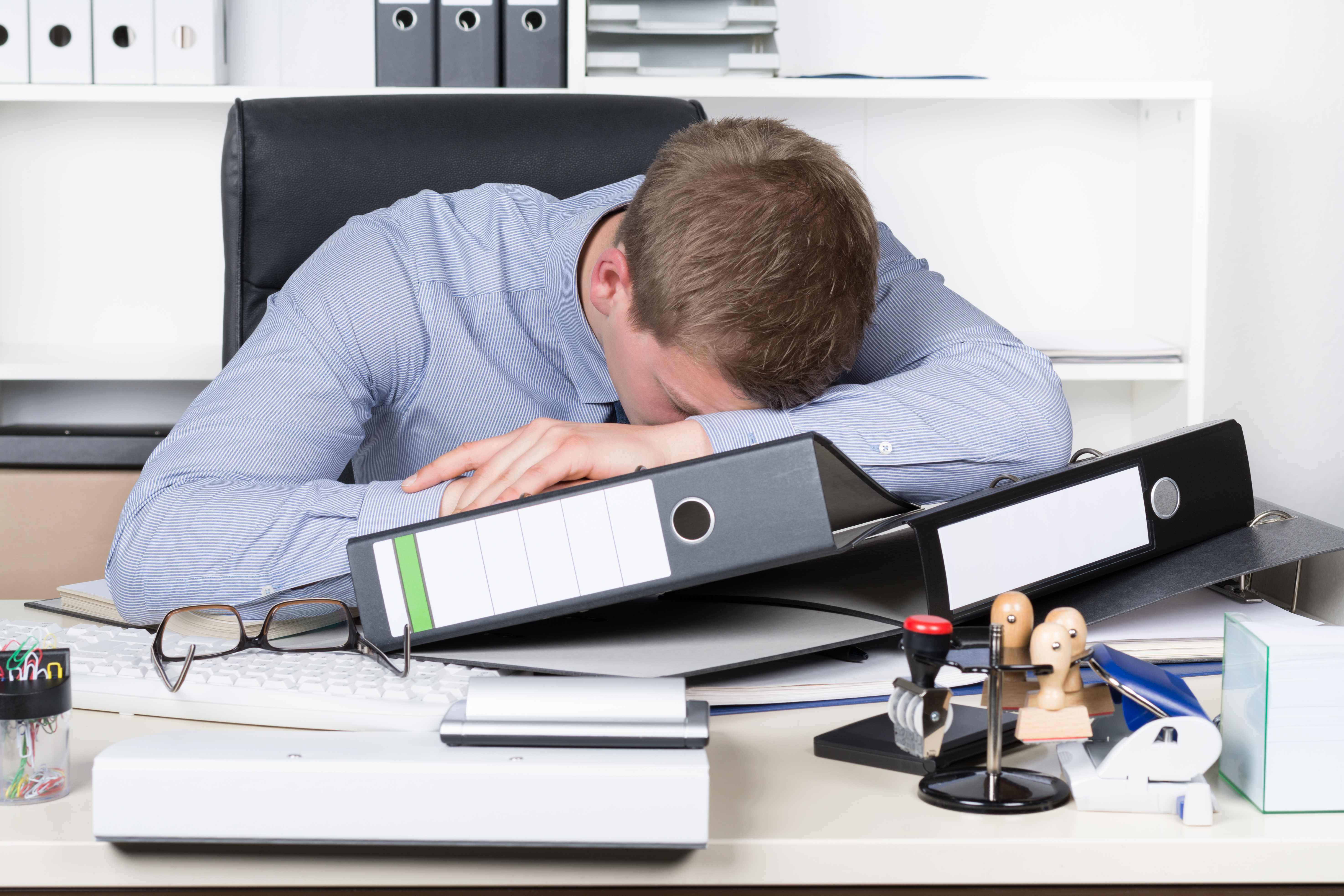 a businessman tired and resting on his desk with a pile of work (