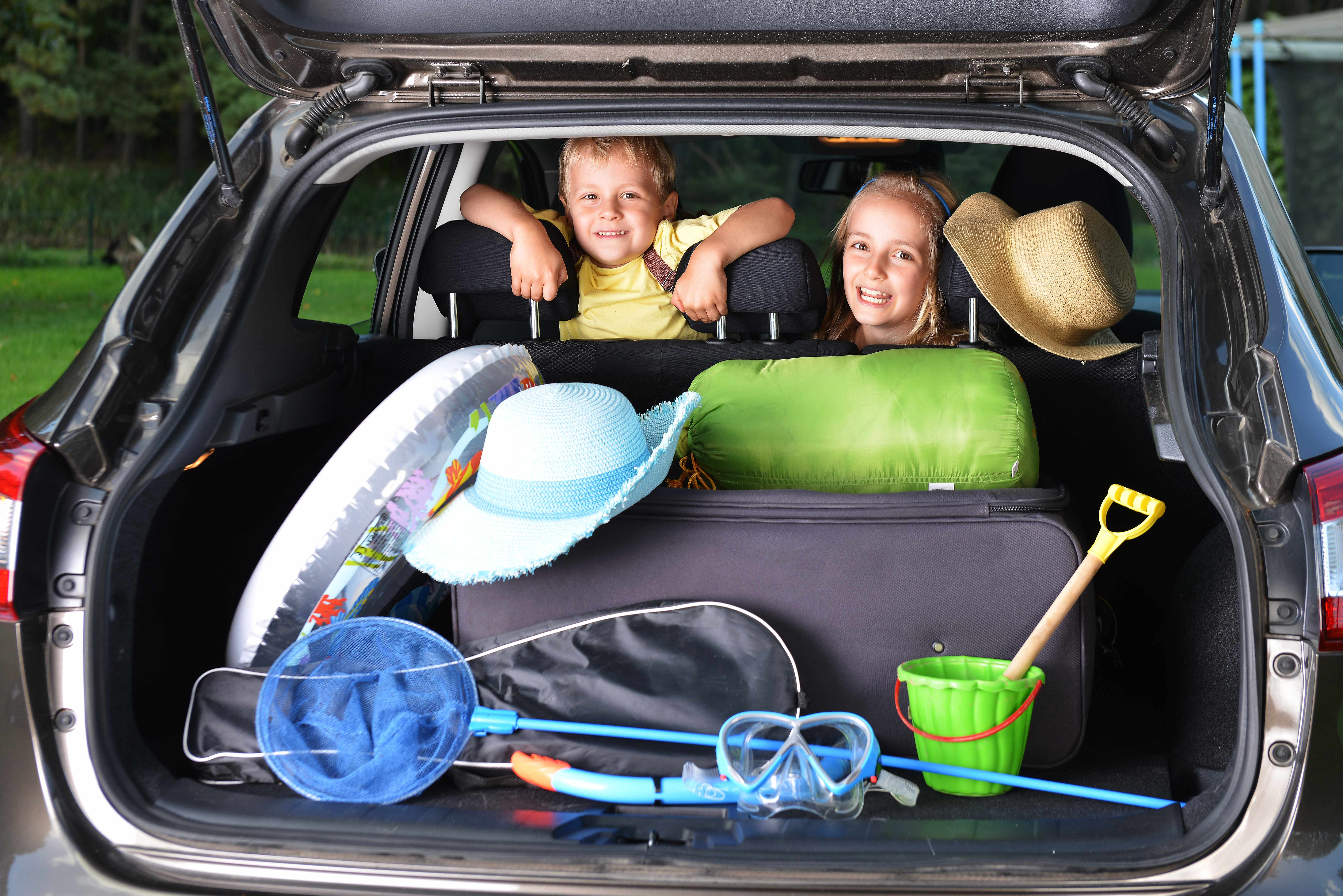 two children in a car with beach toys and vacation items packed in the back