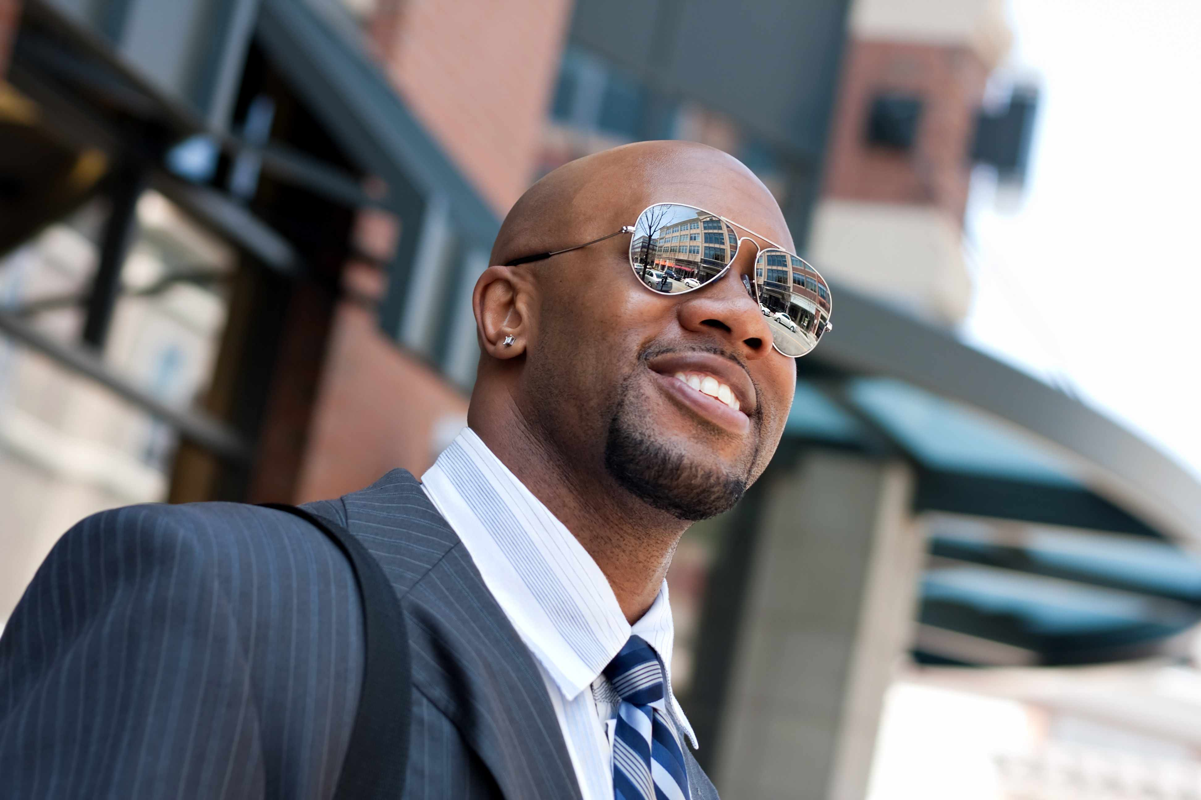 an African-American businessman in a suit wearing sunglasses