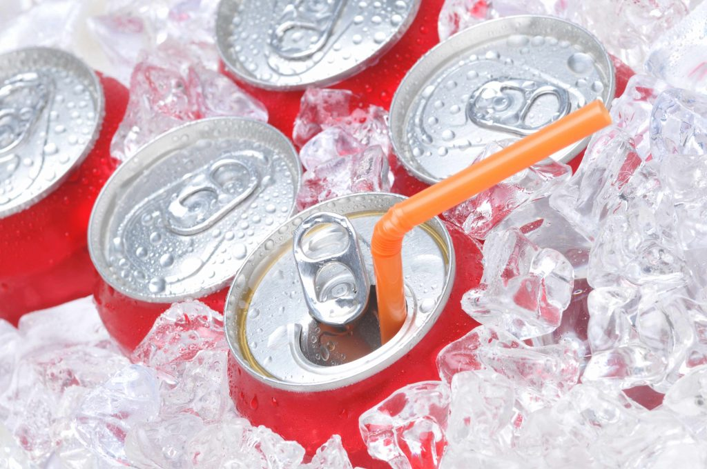 the tops of several cans of soda, packed in ice, one opened and with an orange straw in the top