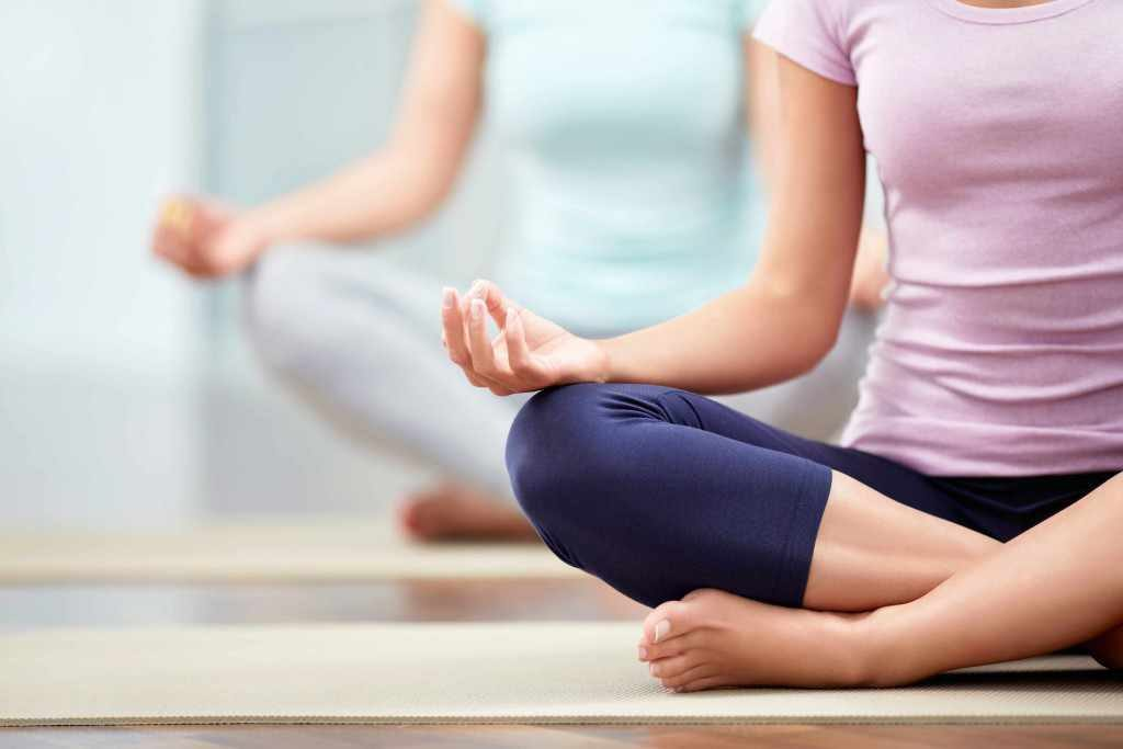 yoga exercise class with people sitting on floor, alternative medicine