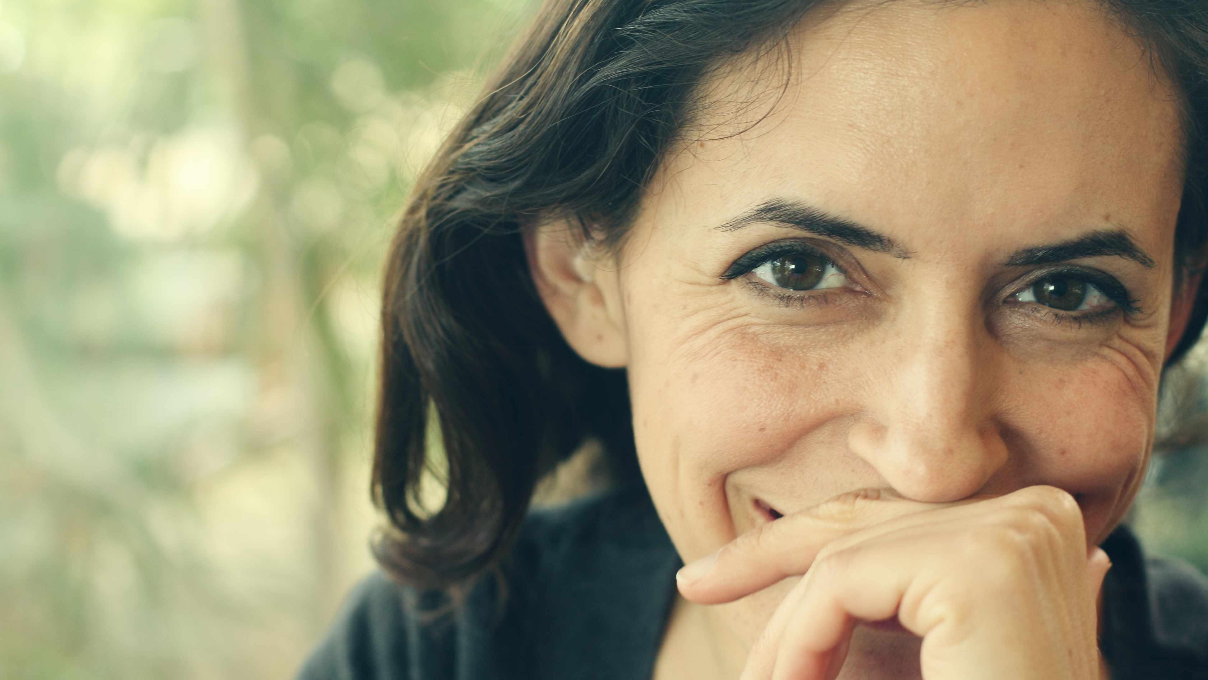Acercamiento de una mujer de mediana edad que sonríe afuera