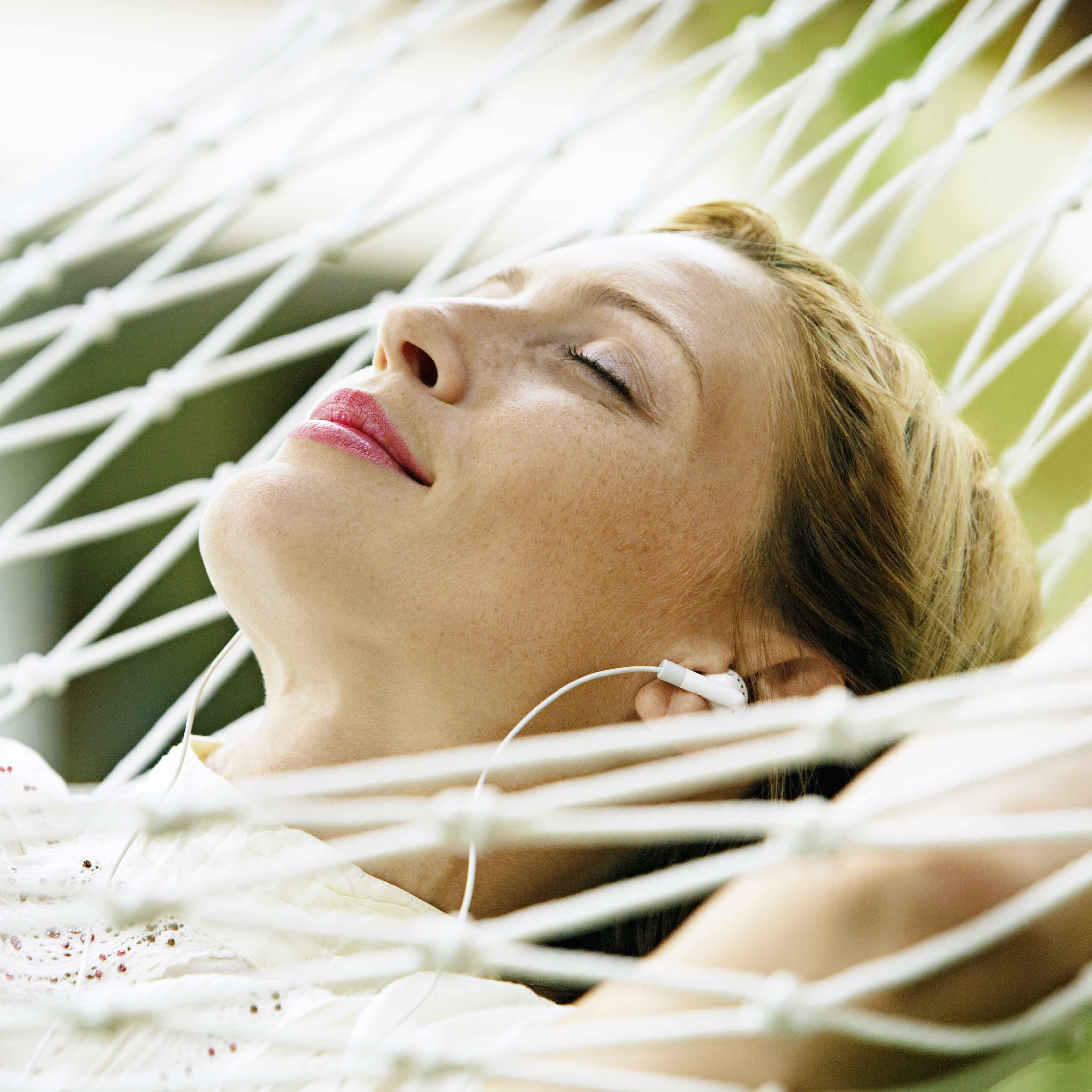 a close-up of a woman relaxing in a hammock, eyes closed, smiling, with earbuds in her ears