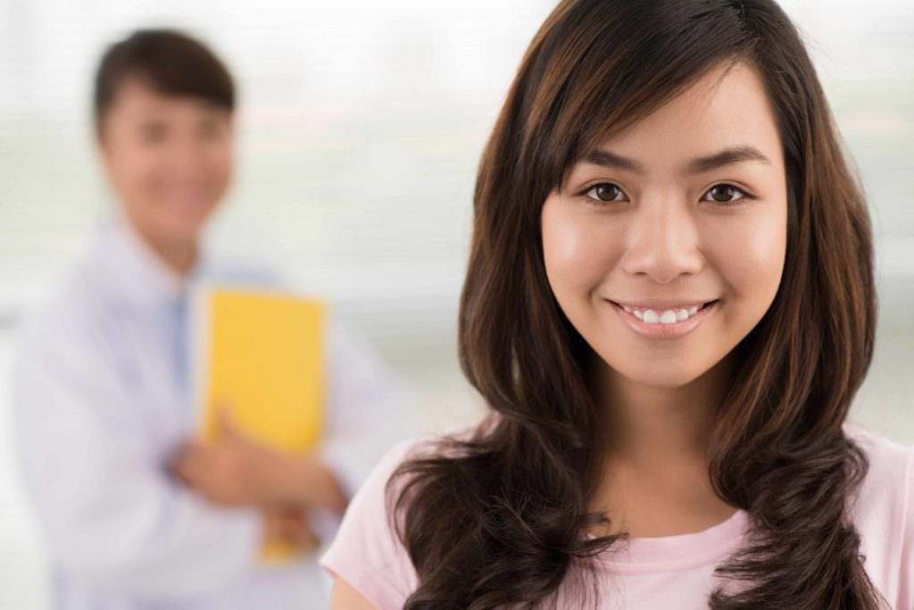 a close-up of a smiling young woman in the foreground, with a physician in the background