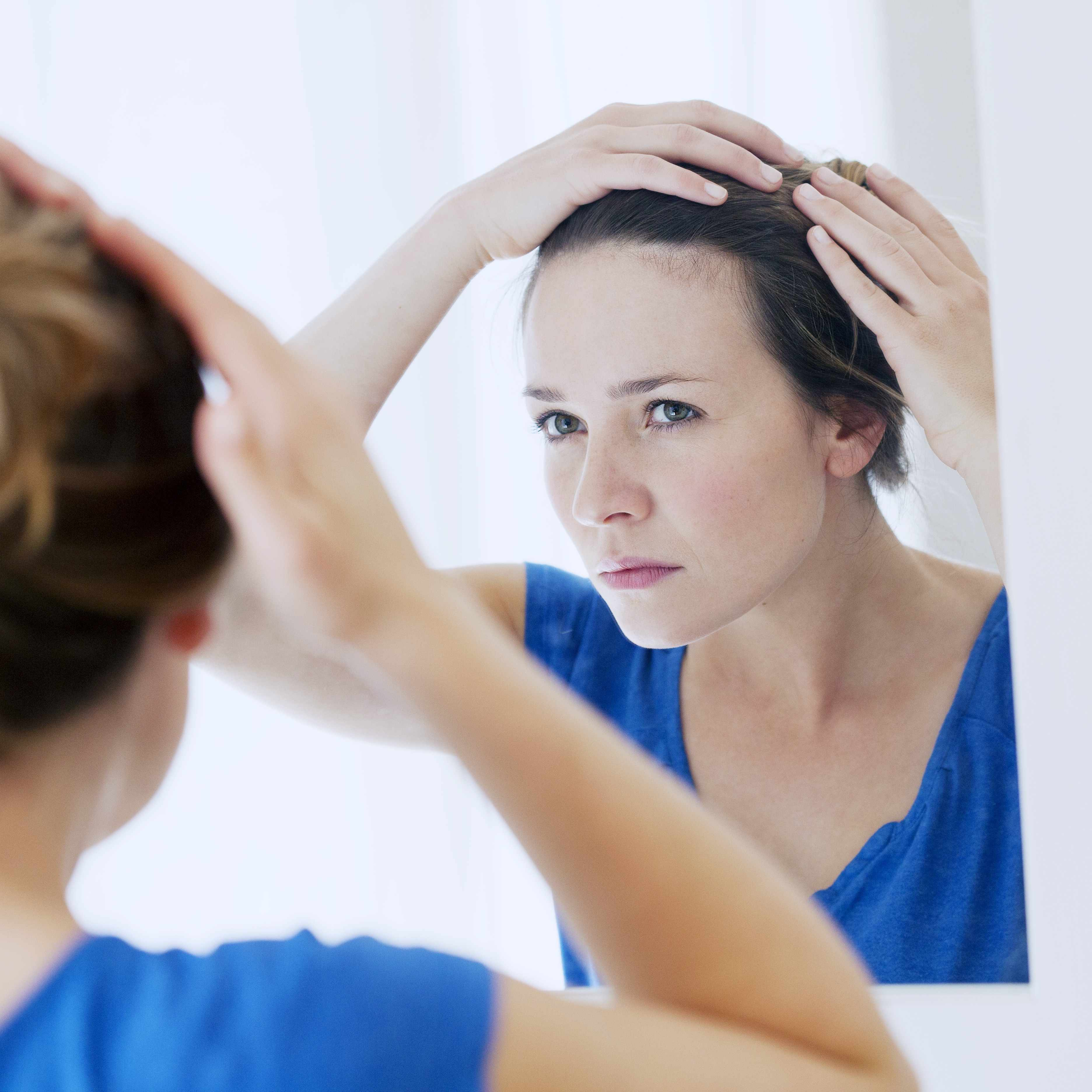 a woman looking at herself in a mirror, examining her hair and scalp