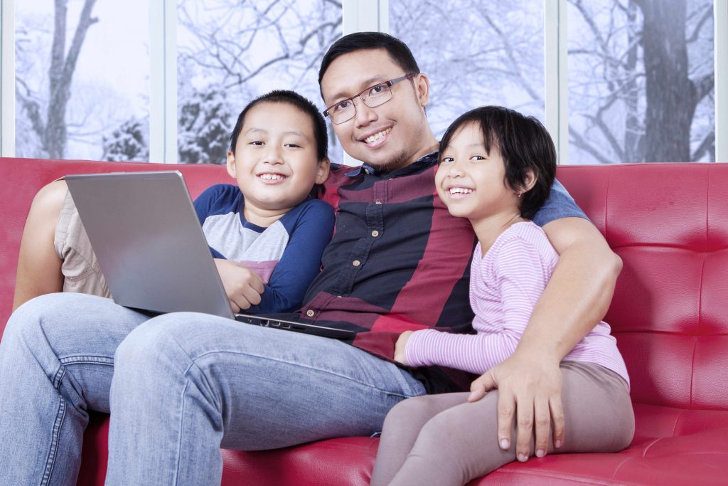 a young father, with a young son and daughter, sitting on a couch, with a laptop on his lap, smiling and relaxed
