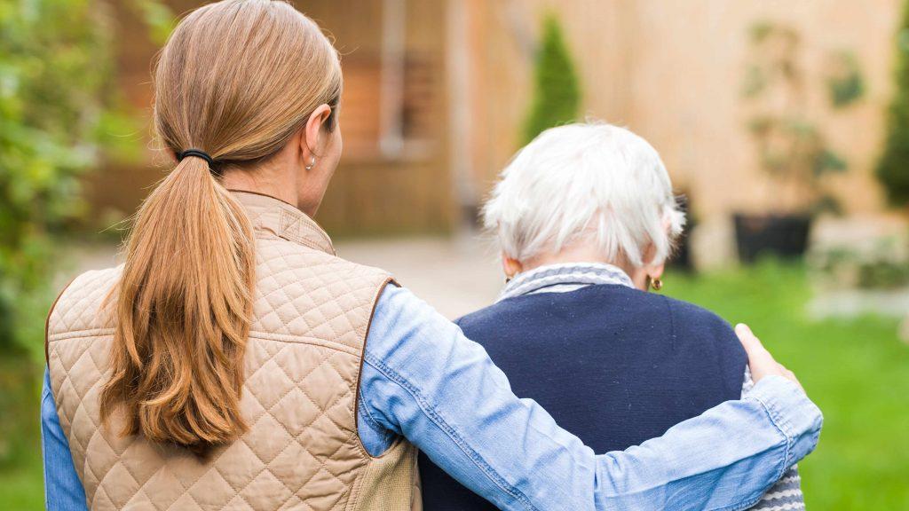 Una mujer joven pone el brazo alrededor de los hombros de una anciana mientras caminan afuera, alejándose de la cámara