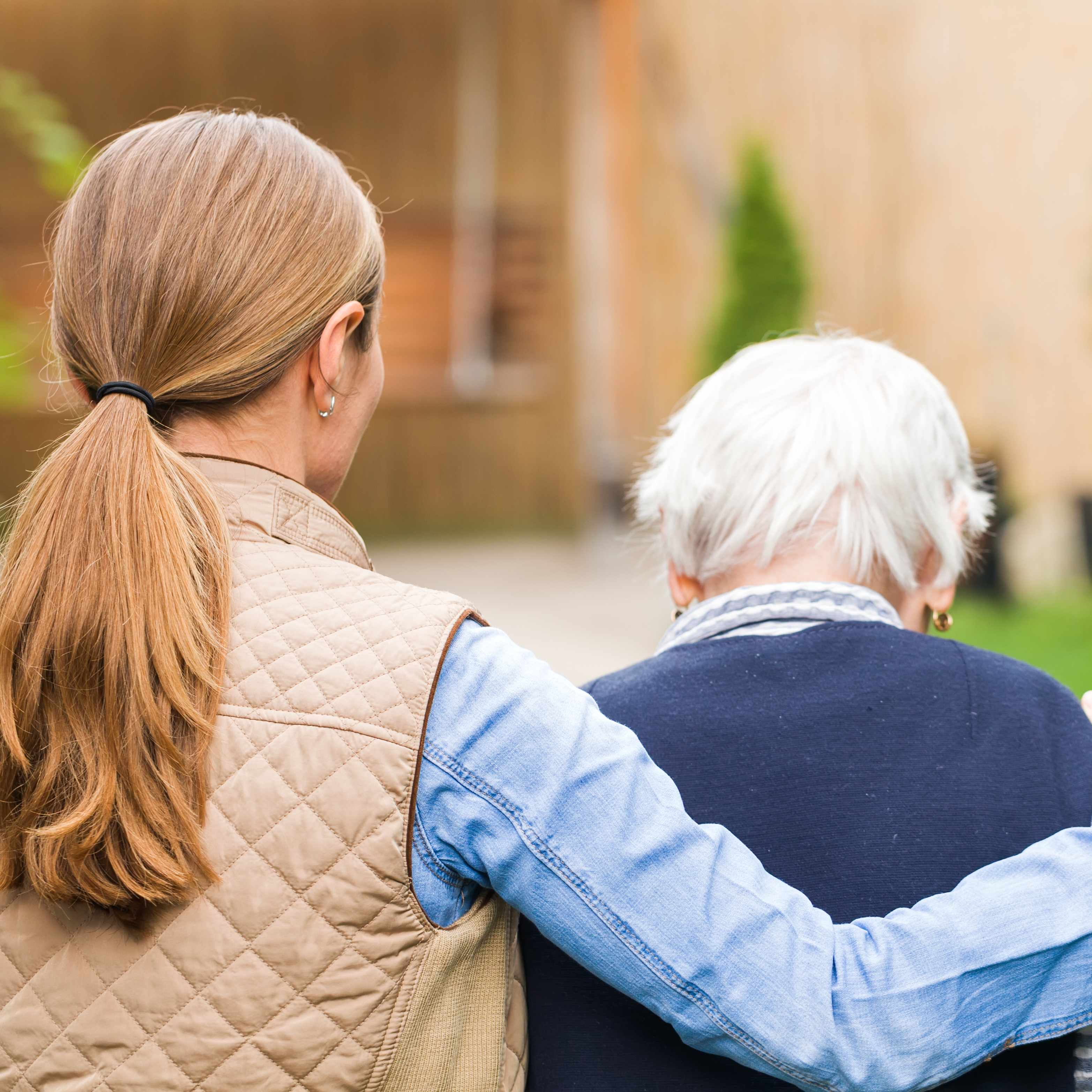 a young woman with her arm around the shoulders of an elderly woman, walking outside, facing away from the camera