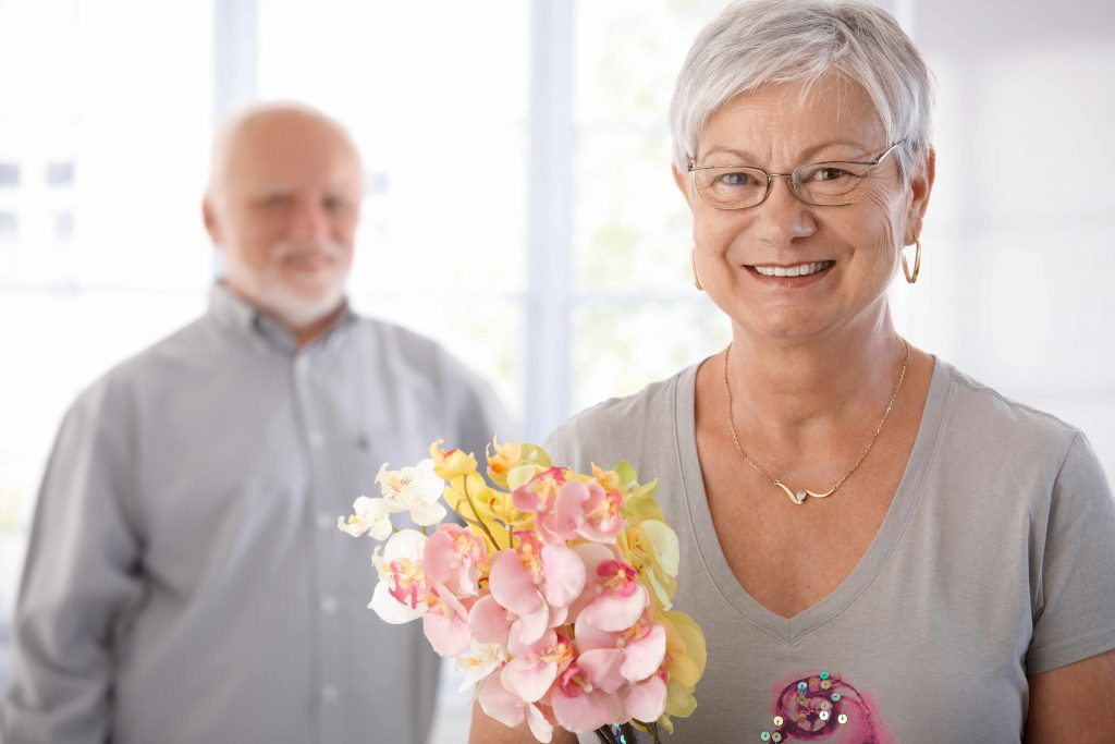 an older couple, she in the foreground smiling, with flowers, he in the background, slightly out of focus