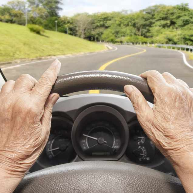 a close-up of an older woman's hands on a steering wheel and the view of the road ahead through the car windshield