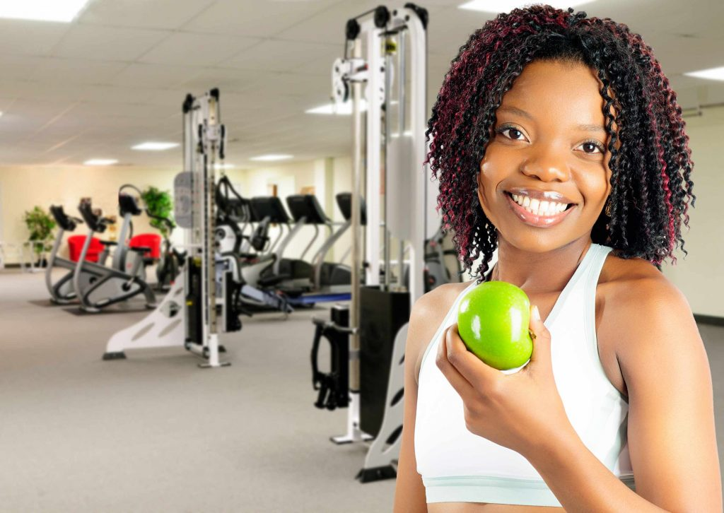 a woman holds an apple at a gym in front of workout exercise machines and treadmills