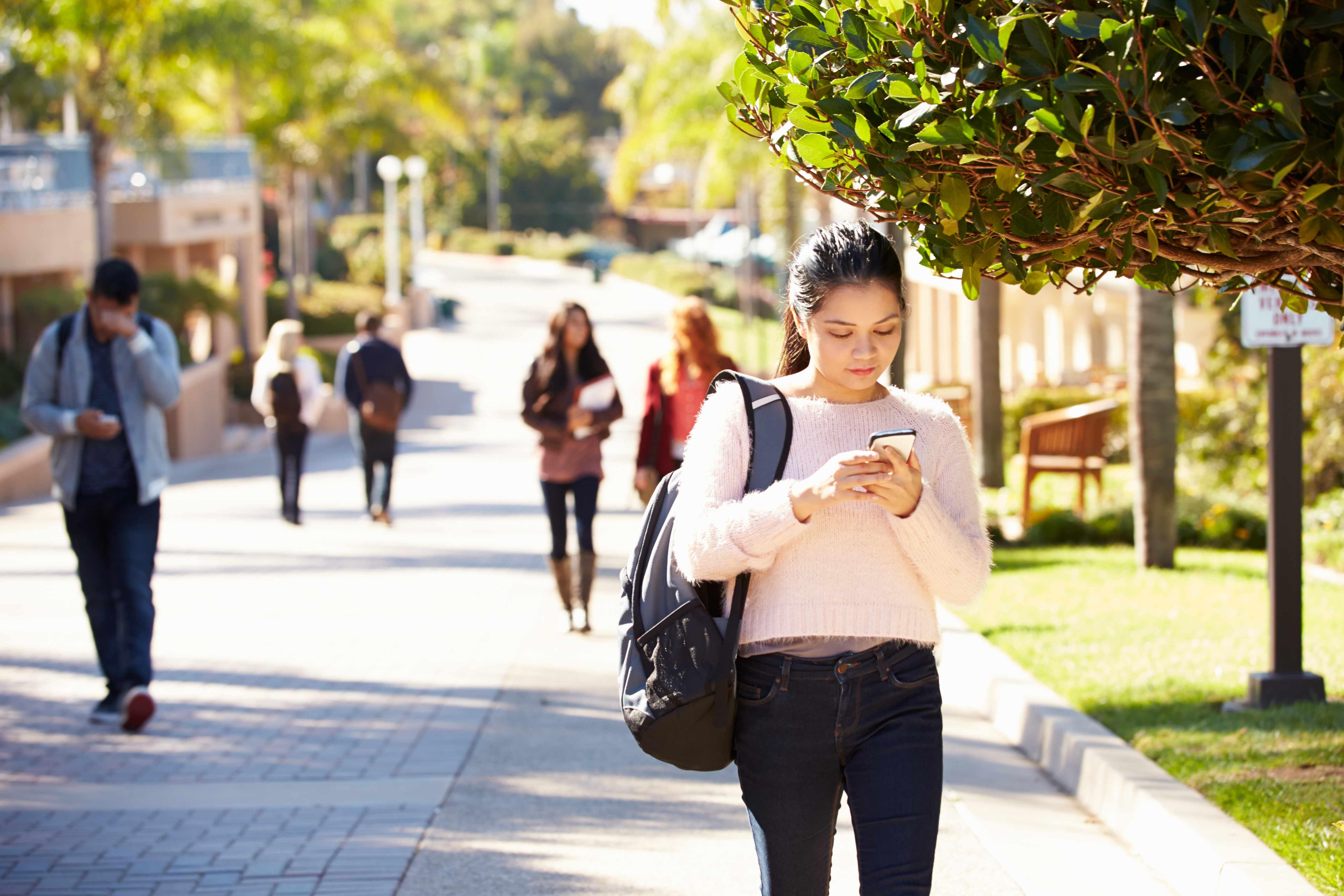 people walking on a sidewalk, some on their phones