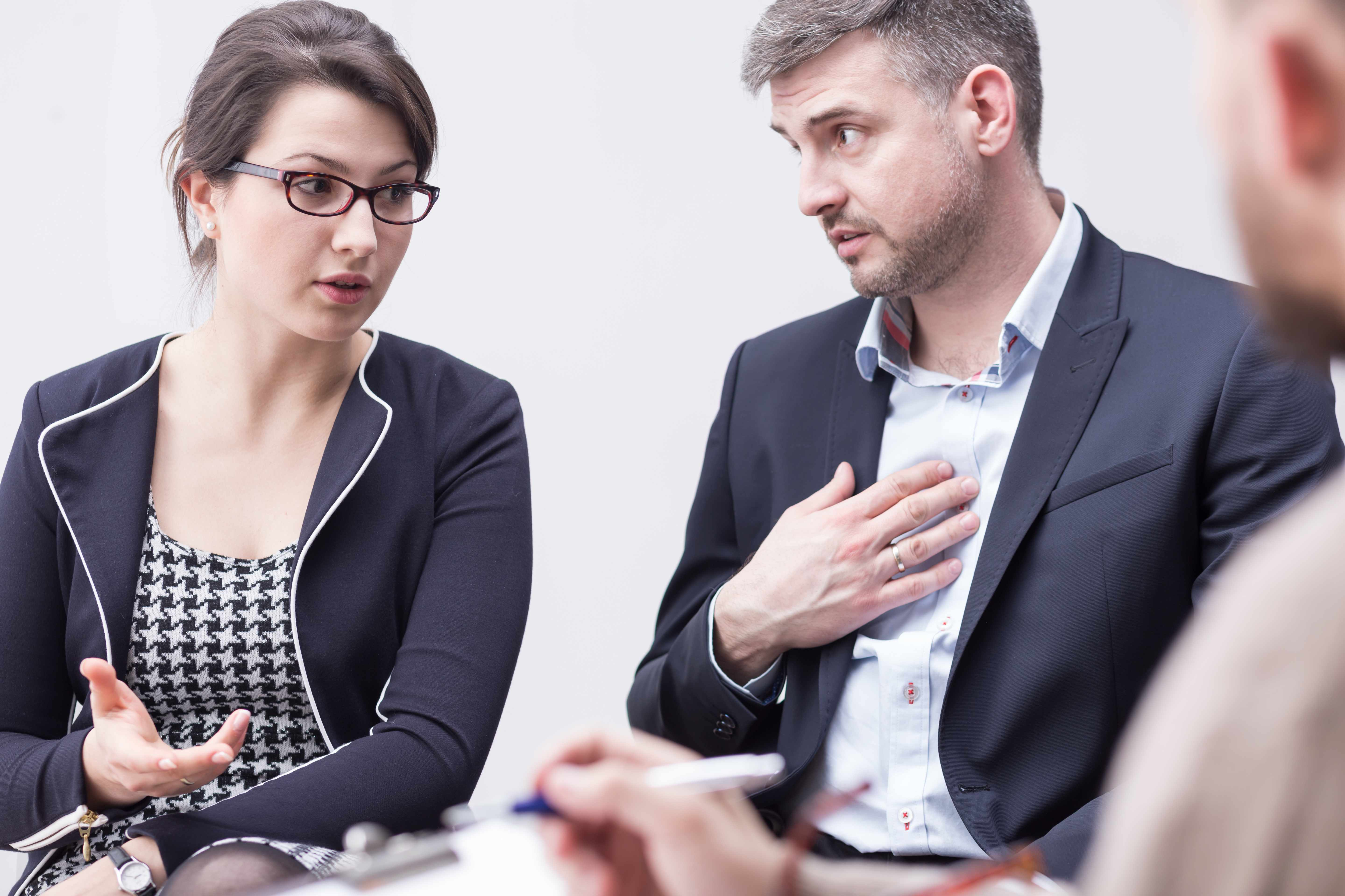 a young couple in a counseling session disagreeing and discussing problems, blaming each other