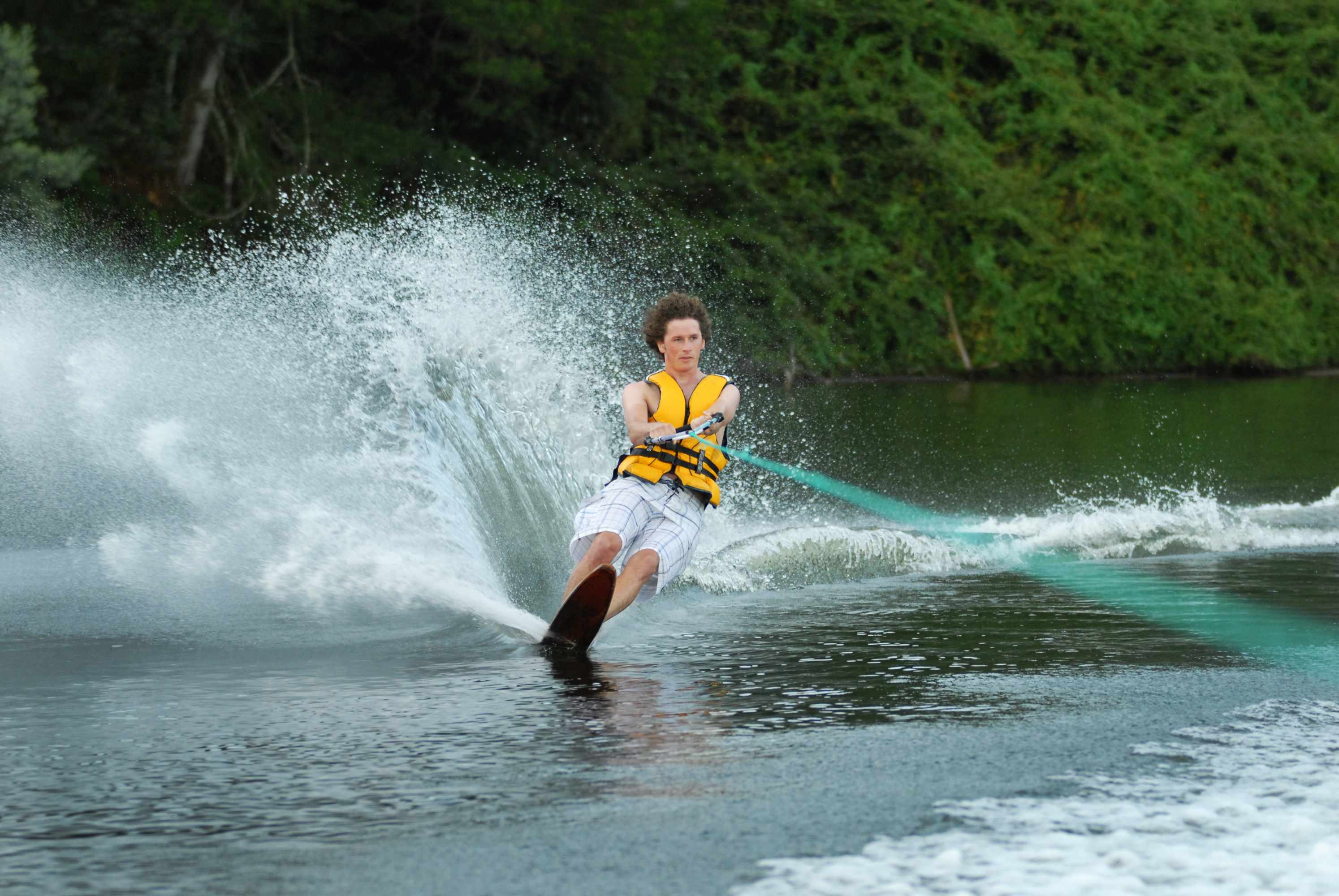 a boy teenager water skiing wearing a life jacket