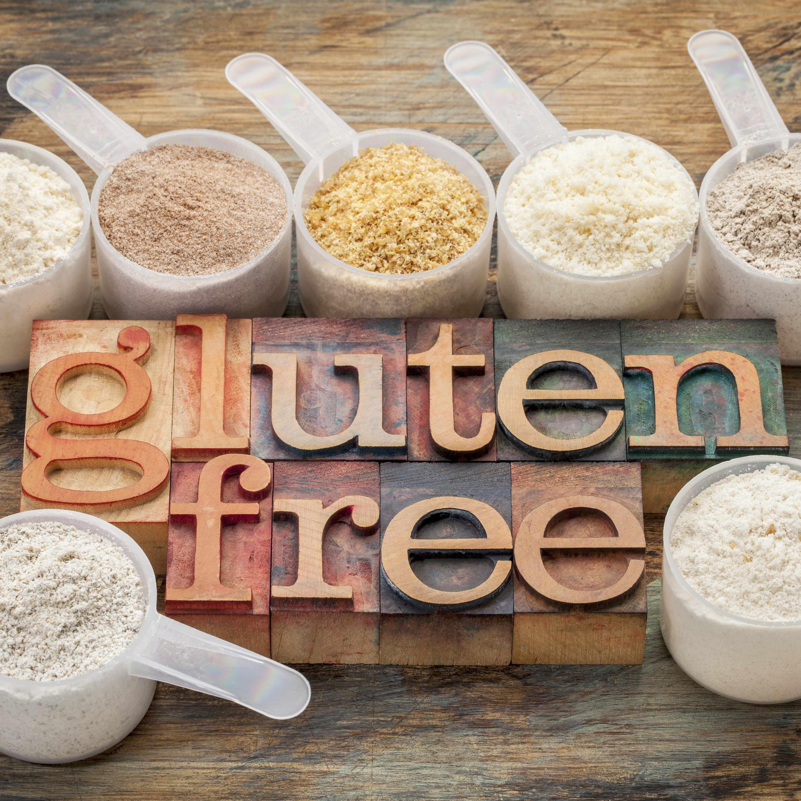 the words gluten free surrounded by scoops filled with various gluten free flours, including almond, coconut, teff, flaxseed meal, rice and buckwheat