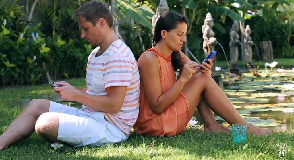 young couple sitting back to back on cell phones multitasking