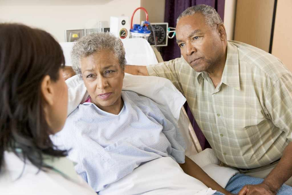 African-American woman and man in hospital bed listening to doctor