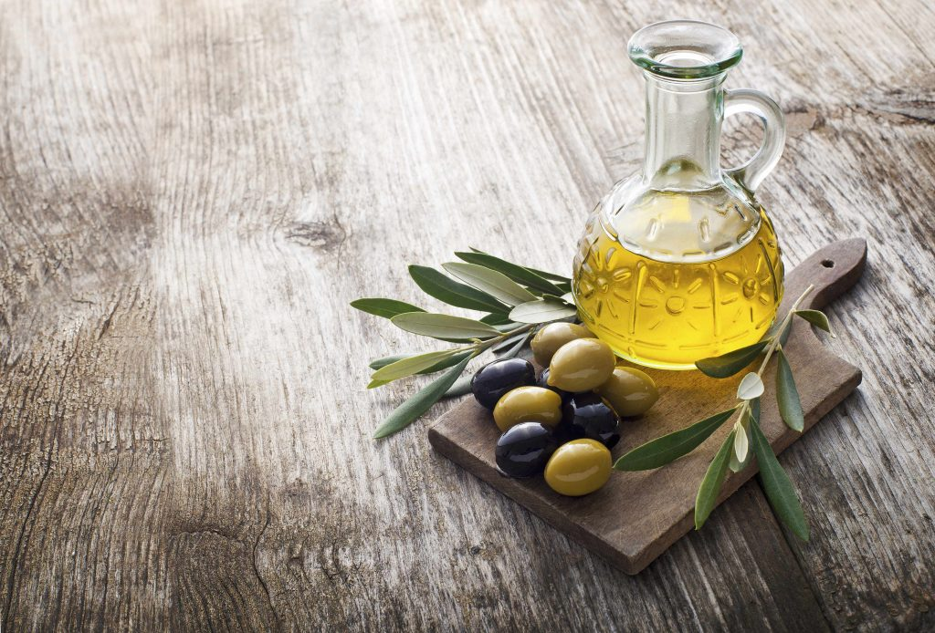 a flask of olive oil on a wooden cutting board, with olives and olive leaves