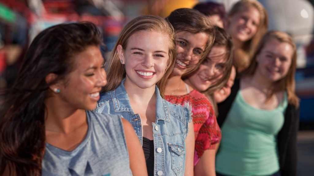 Un grupo de adolescentes sanas y sonrientes que hacen fila una detrás de la otra