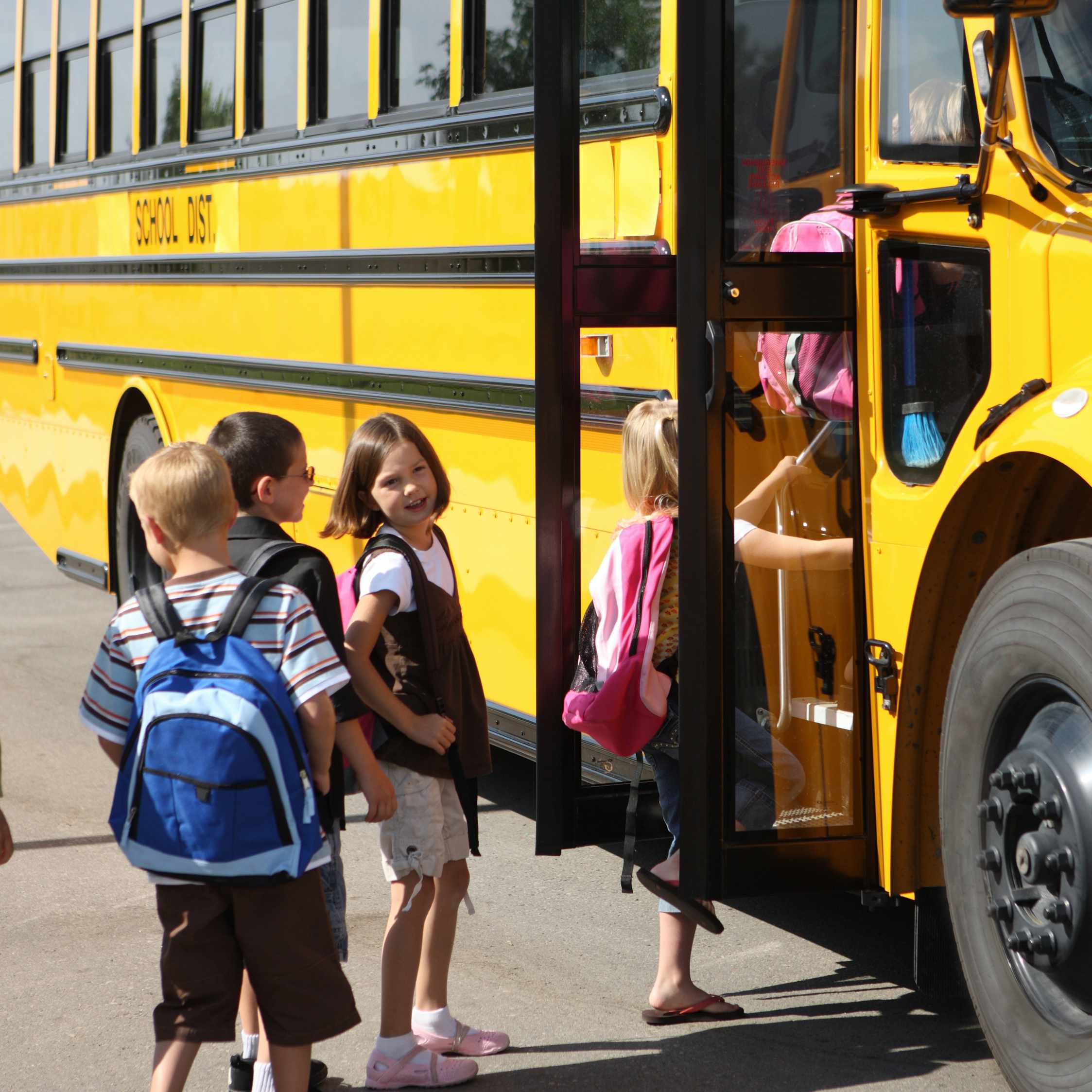 a group of young elementary school children with backpacks, getting on a school bus