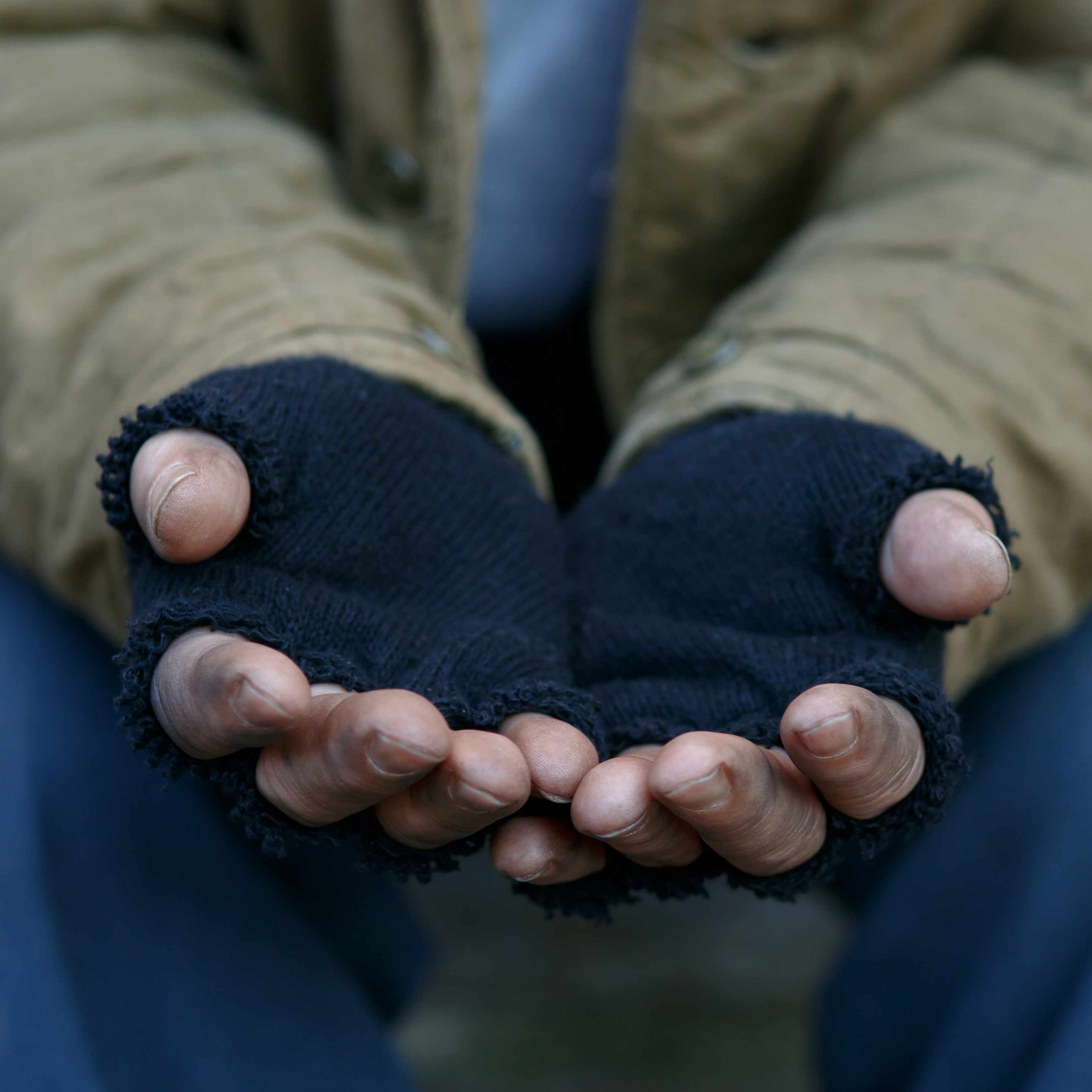 a homeless man holding out his hands for help