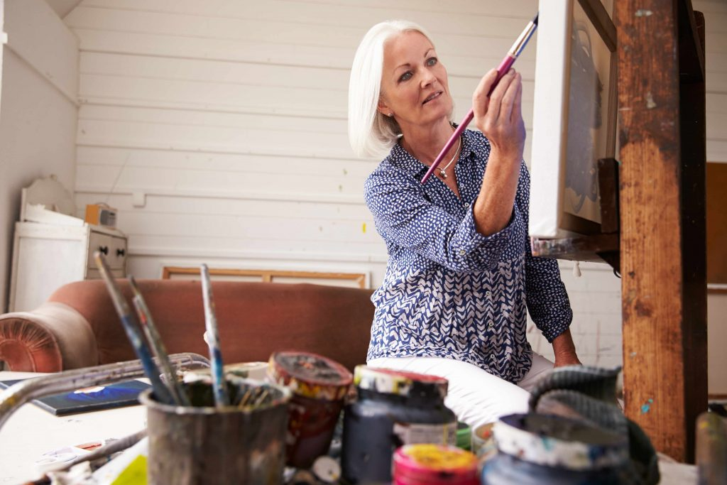 a middle-aged woman working on a painting in a studio