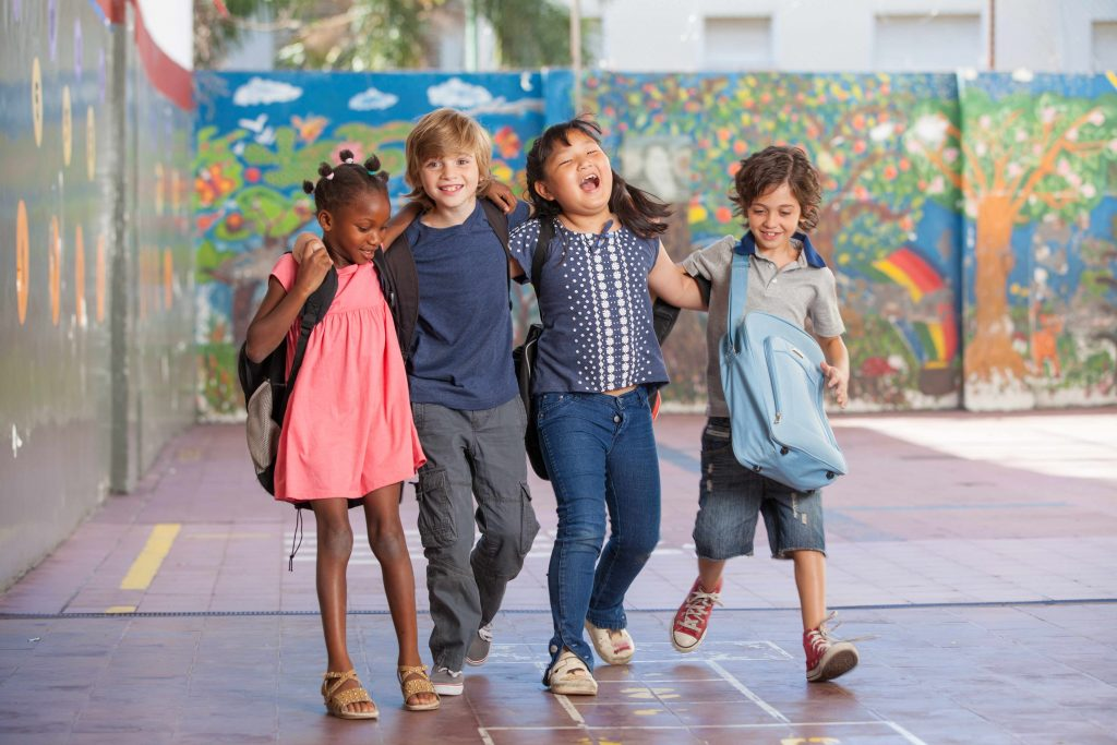 a multiracial group of four children, girls and boys, walking arm-in-arm in a schoolyard