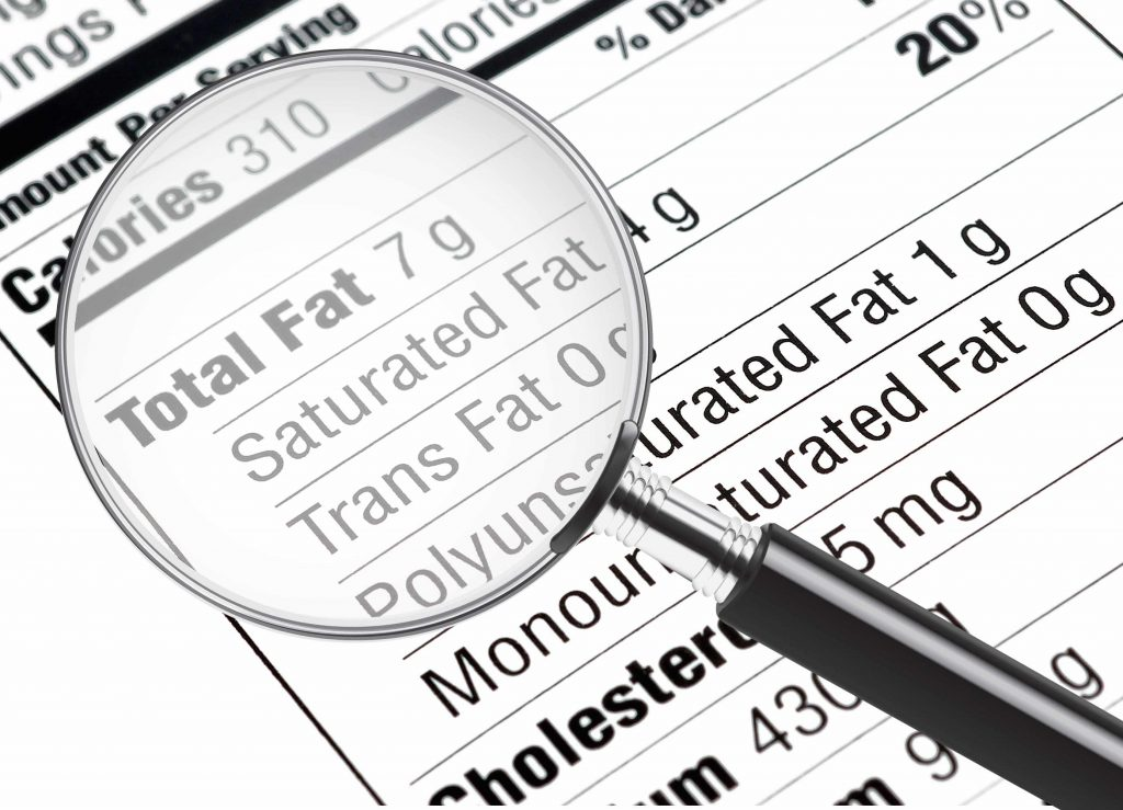 a nutrition information label with a magnifying glass highlighting the fat content, including Trans Fat 0 g