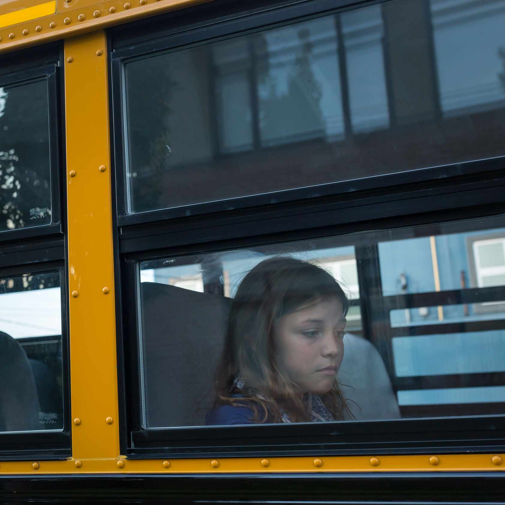 a sad elementary school girl on a bus