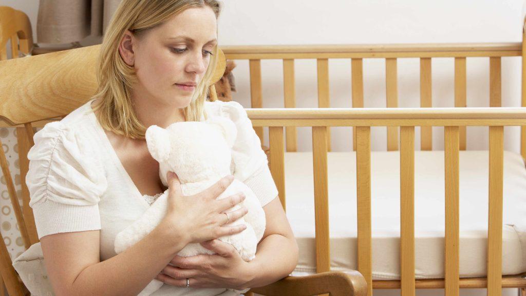 Una mujer triste con un oso de peluche en los brazos y sentada en una mecedora junto a una cuna vacía