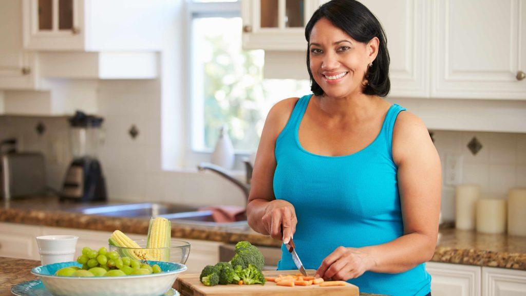 Una mujer de mediana edad sonriente y con exceso de peso prepara la comida en la cocina