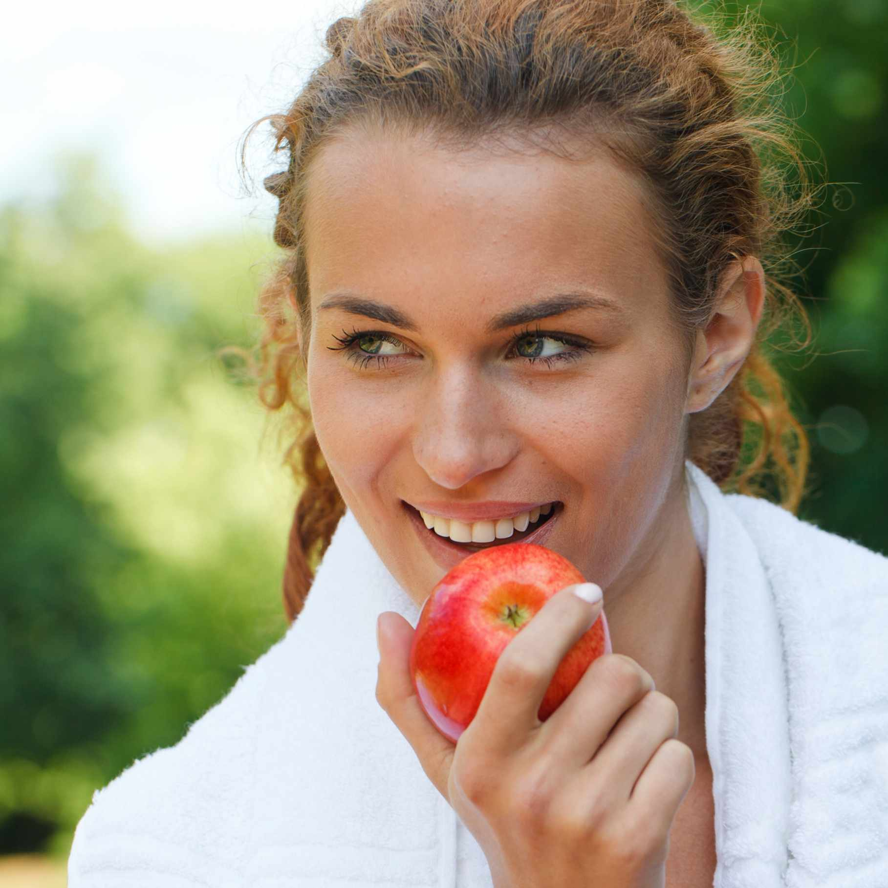 a woman eating an apple for good health and nutrition after exercising